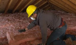 Kitchener Affordable Roofing worker installing insulation