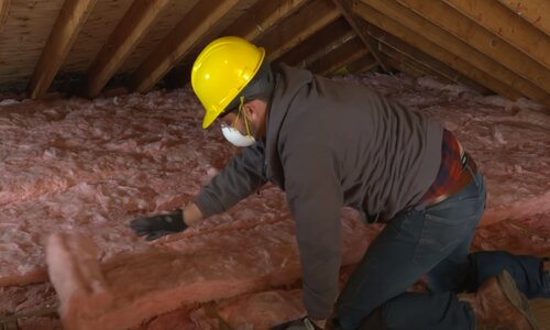 Kitchener Affordable Roofing worker installing insulation
